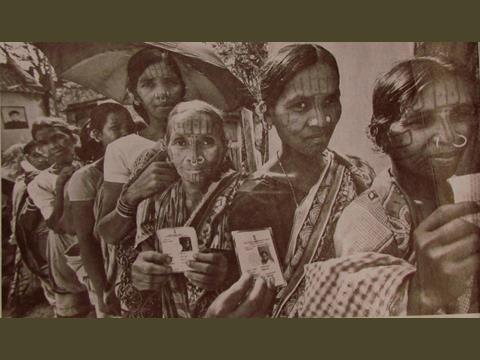 Image 4: Indigenous women of the Kandha tribe display their voter's identity cards as they     wait to cast their votes outside a polling station during Indian parliamentary elections in        Dingesiguda Village, Orissa State, India.    Source: The Epoch Times, April 11, 2014